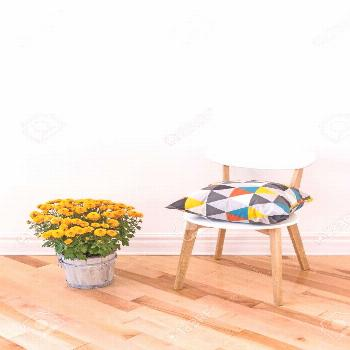 Bright cushion on a chair, and orange chrysanthemums decorating a room. Stock Photo ,